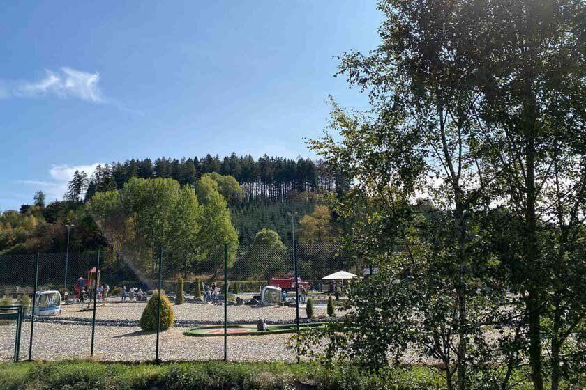 Blick von außen durch den Zaun zum AdventureGolf in Winterberg-Hildfeld