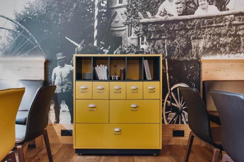 Nachgebauter Postschrank vor einer Fototapete mit historischen Aufnahmen im Restaurant Alte Post