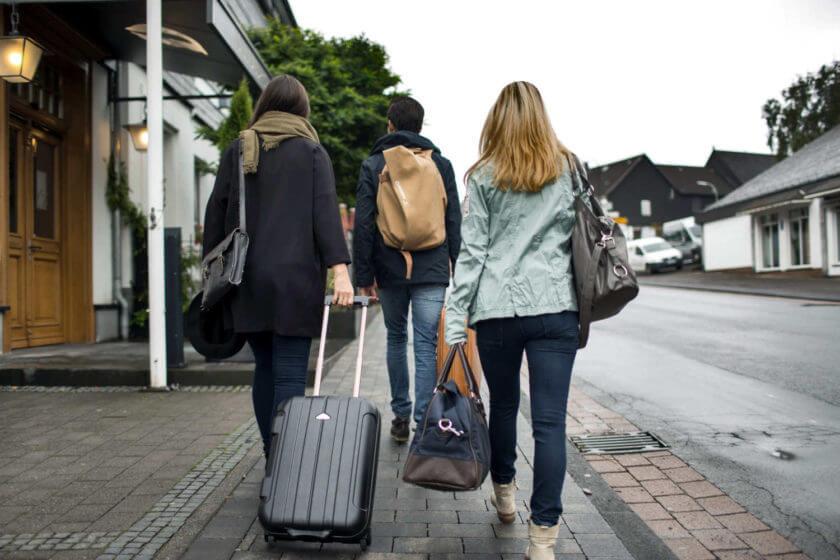 Drei Personen reisen an und gehen mit ihren Koffern die Straße entlang zum Hoteleingang