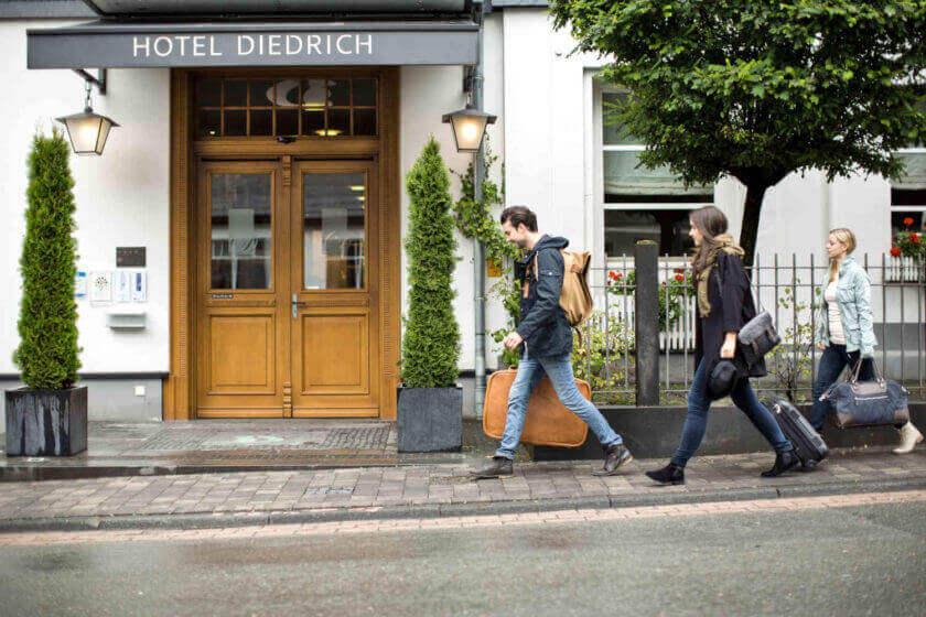 Drei Personen reisen an und gehen mit ihren Koffern auf den Hoteleingang zu