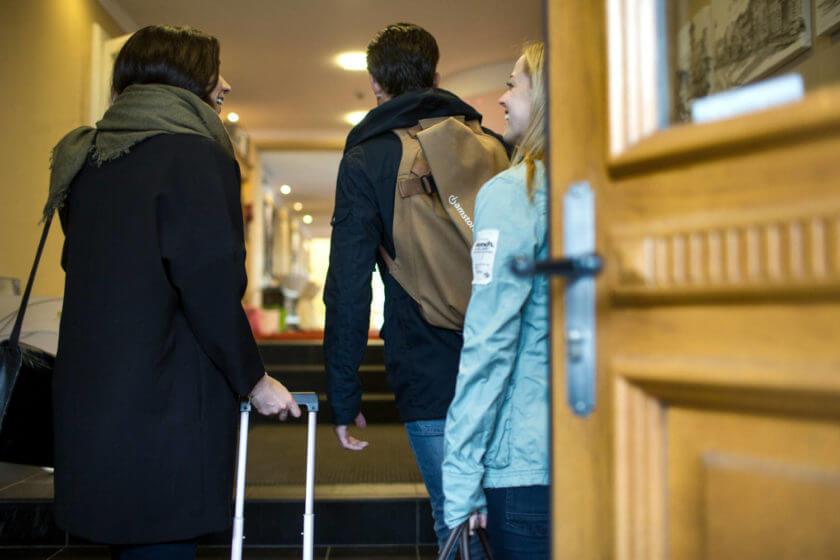 Drei Personen sind mit Koffern durch den Hoteleingang gegangen
