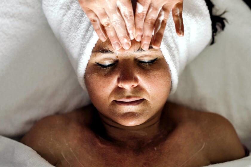 Eine liegende und in Frottee gewickelte Frau bekommt eine Stirnmassage