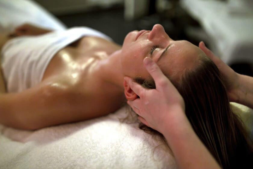 Eine auf dem Rücken liegende Frau erhält eine Kopfmassage