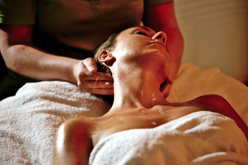 Eine Frau liegt auf der Wellnessliege und erhält eine Nackenmassage
