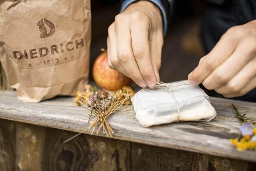 Brot wird draußen in ein Brotpapier geschnürt daneben eine Tüte mit DIEDRICH-Logo