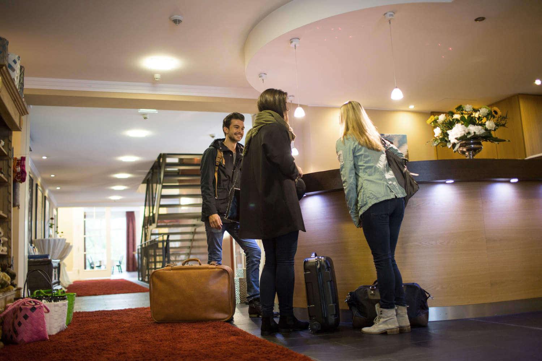 Drei Personen unterhalten sich an der Hotelrezeption