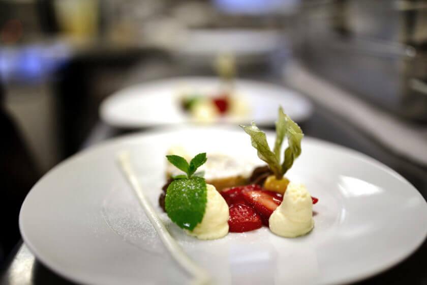 Zwei Dessertteller mit weißem Schokoladenmousse und frischen Erdbeeren
