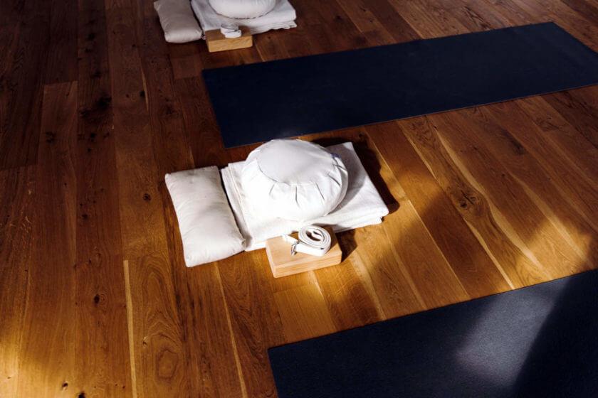 Auf dem Holzboden des Yogaraum liegen im Lichteinfall Matten, Kissen und Decken bereit
