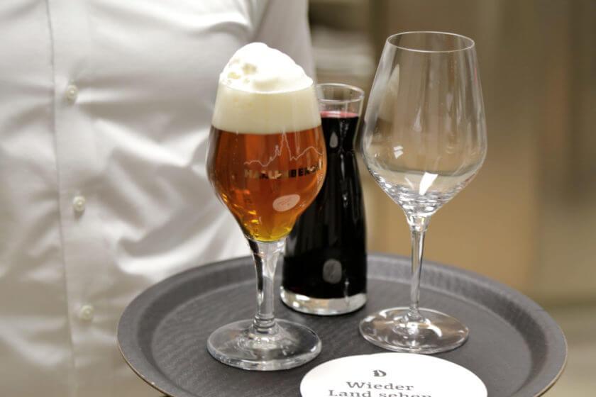 Ein Tablett mit Hallenberger Landbier und Rotwein wird getragen
