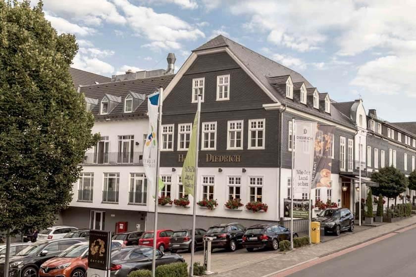 Außenansicht des Hotel Diedrich mit vollem Parkplatz und Fahnen