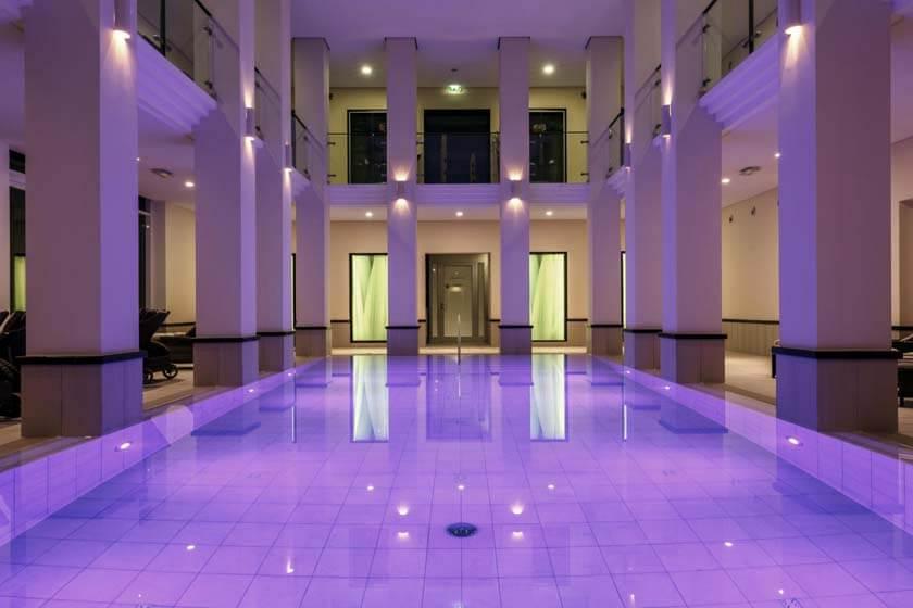 Innenpool des Wellnesshotel Diedrich im Sauerland bei violettem Farblicht am Abend