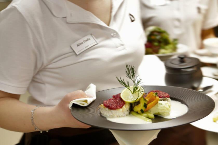 Eine Kellnerin trägt einen Seeteufel unter der Rote Bete Kruste auf einem schwarzen Teller