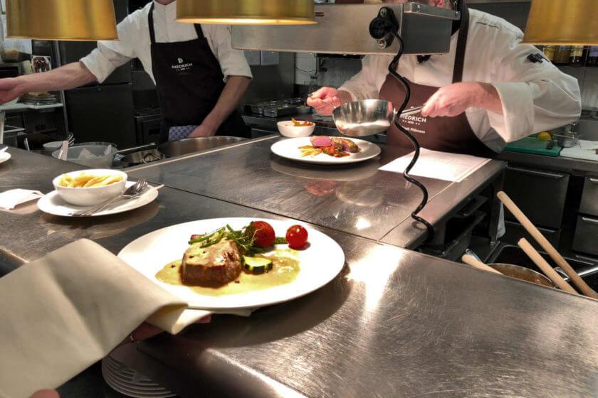 Zwei Hauptgerichte sind servierfertig angerichtet und werden vom Kellner aufgenommen