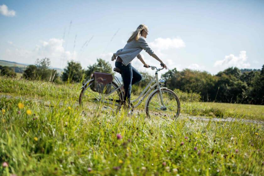 Eine Frau fährt auf dem Fahrrad über den sommerlichen Feldweg