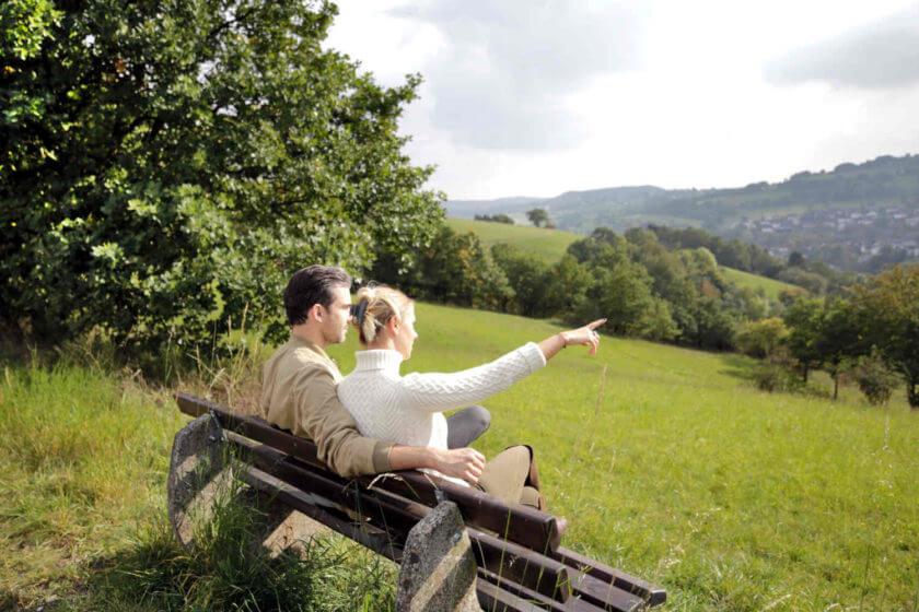 Ein Paar sitzt auf der Wanderbank und zeigt in die Ferne