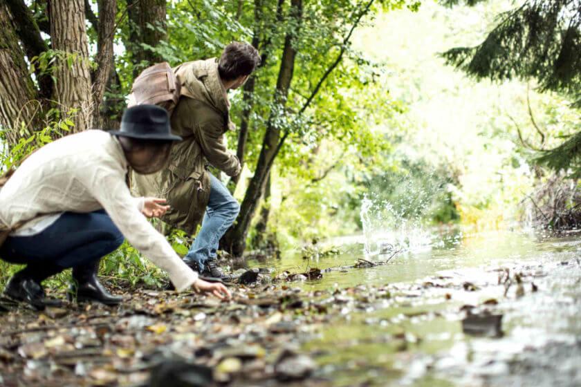 Ein Paar hockt am Bachlauf und flitscht Steine