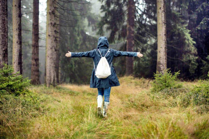 Eine Frau steht im saftig grünen Wald und streckt beide Arme frei von sich
