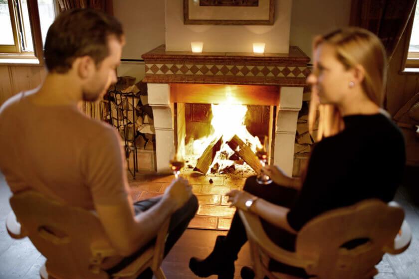 Ein Paar sitzt am Kaminfeuer und genießt einen Digestif