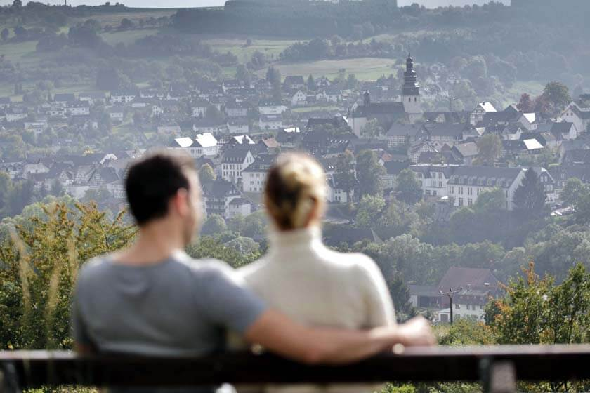 Ein Paar sitzt auf einer Bank am Wanderweg und Blickt auf das Fachwerkstädchen Hallenberg bei klarem Sommerwetter
