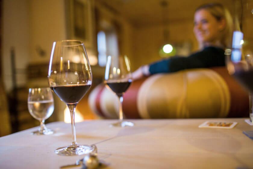 Zwei Rotweingläser auf dem Tisch und im Hintergrund eine Frau, die im Sessel entspannt