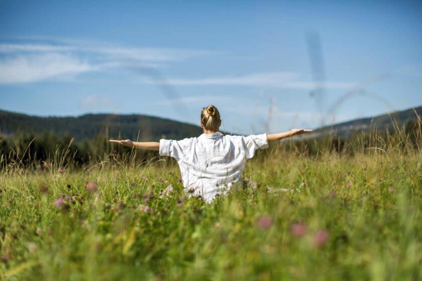 Eine Frau sitzt bei klarem Sommerwetter im hohen Gras und streckt beide Arme von sich