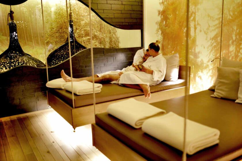 Ein Paar liegt im Ruhebereich auf einem Bett, er schläft während sie liest