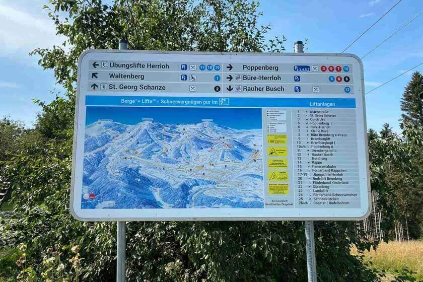 Eine großes Kartenschild mit den abgebildeten Liftanlagen neben der Sprungschanze in Winterberg