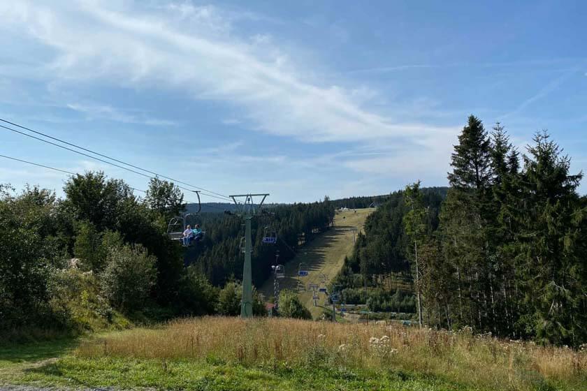 Menschen fahren mit dem Sessellift hinauf zur Sprungschanze in Winterberg
