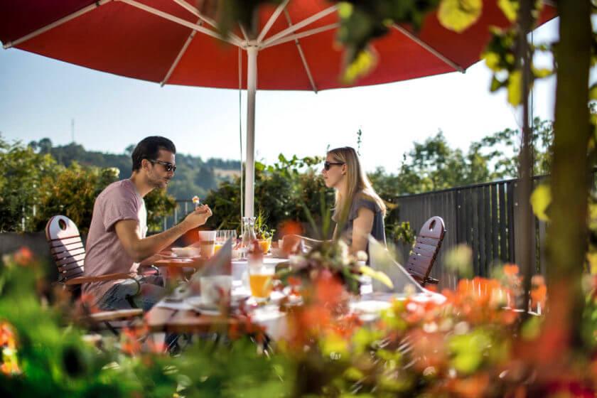 Ein Paar frühstückt bei bestem Sommerwetter auf der Terrasse unter einem roten Sonnenschirm