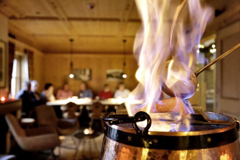 Aufflammende Feuerzangenbowle, im Hintergrund eine Hand voll Gäste am großen Tisch
