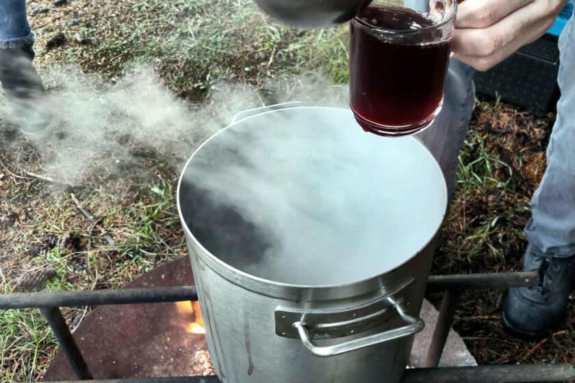 Ein dampfender Kochtopf, aus dem Glüchwein geschöpft wird, steht im Winter auf einer Feuerschale