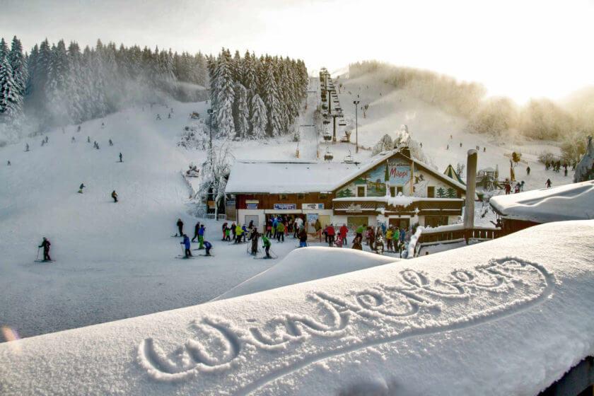 Der Schriftzug Winterberg im satten Schnee, im Hintergrund ein belebter Skihang