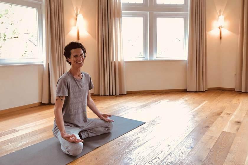 Lächelnder Yogalehrer im Lotussitz