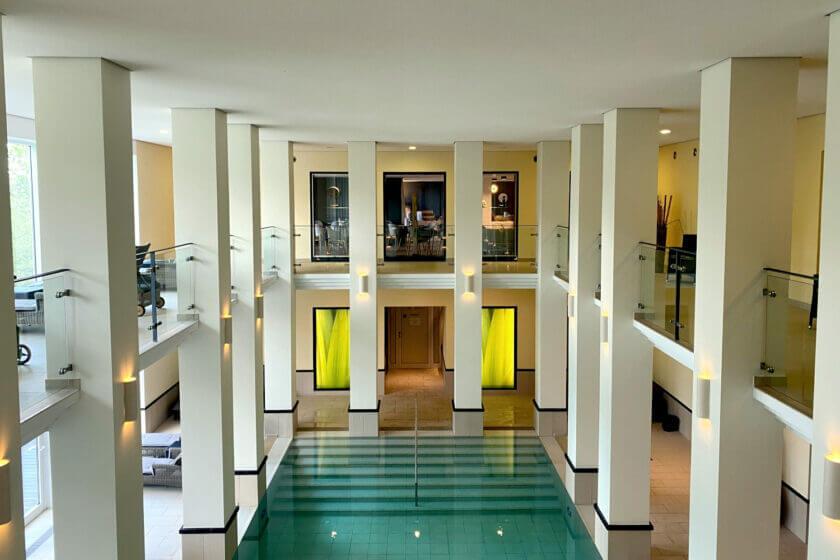 Innenpool mit säulenumrahmtem Luftraum und umlaufender Empore im Hotel Diedrich