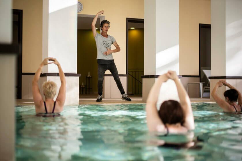 Der Kursleiter steht am Rand des Innenpools und macht den Teilnehmern die Aquagymnastik-Übungen vor im Hotel Diedrich
