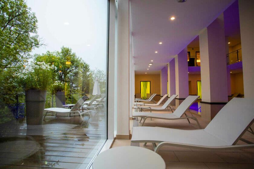 Ruheliegen spiegeln sich in der großen Fensterfront beim lilablau leuchtenenden Innenpool im Hotel Diedrich