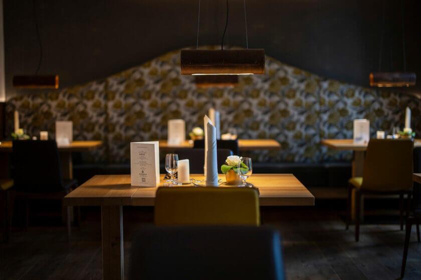 Beleuchteter und eingedeckter Tisch mit Menükarte im Restaurant Alte Post des Hotel Diedrich