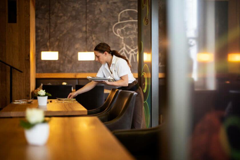 Eine Restaurantmitarbeiterin beugt sich vor und deckt einen Tisch für das Abendgeschäft ein - Hotel Diedrich