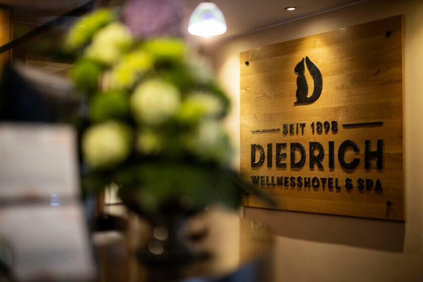 Große Holztafel mit dem schmiedeeiseren Hotellogo an der Hotelrezeption des Hotel Diedrich
