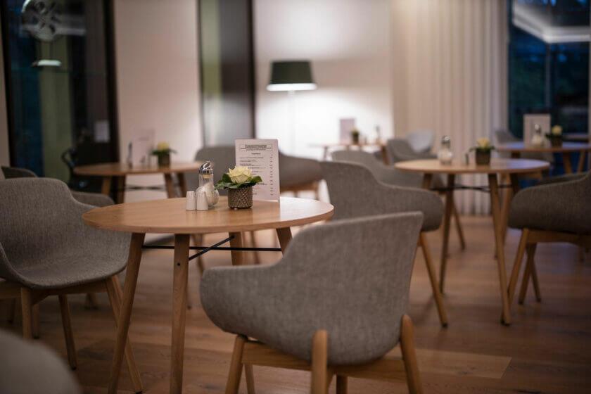 Ein runder Holztisch mit stoffbezogenen Stühlen im Bademantelbistro des Hotel Diedrich