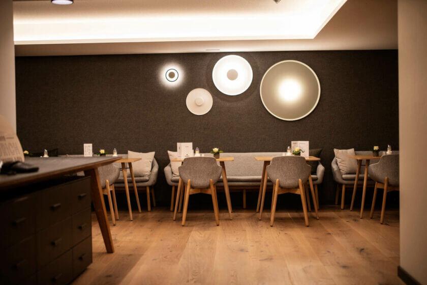 Die Wand des Bademantelbistros mit Wandleuchten und Tischen im Hotel Diedrich